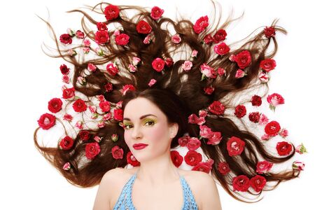 Beautiful girl with bright makeup lying on white background with roses in her hair photo