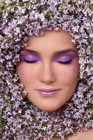 Portrait of beautiful girl with stylish makeup and lilac around her face photo