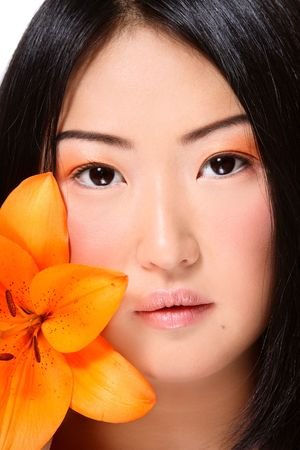 Close-up portrait of beautiful young asian girl with bright flower