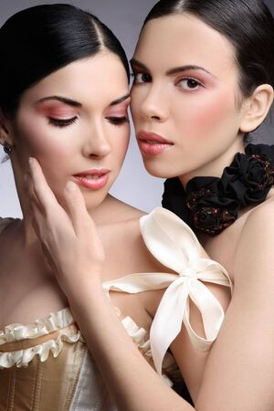 Black and white colored portrait of two beautiful slim sexy young girls with clear pink make-up Stock Photo - 6619381