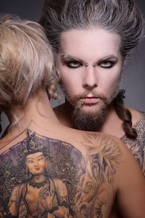 freaks: Portrait of pierced man with old-fashioned make-up and hairstyle embracing blond woman with huge tattoo on her back