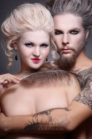 Portrait of pierced tattooed man and woman with old-fashioned make-up and hairstyle  photo