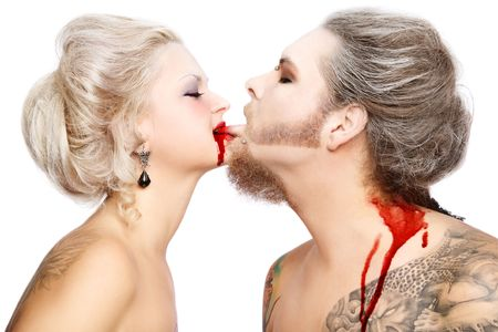 Portrait of pierced tattooed man and woman with old-fashioned make-up and hairstyle playing vampires photo