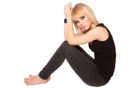 barefoot teens: Beautiful blond slim teen girl with trendy make-up sitting on white background Stock Photo