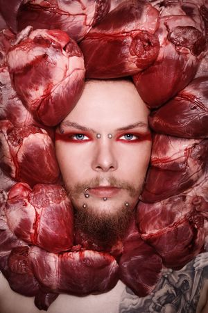 heartbreaker: Conceptual close-up portrait of pierced and tattooed man with raw bloody hearts around his face