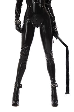 catsuit: Legs of slim sexy woman in black latex catsuit with cuffs and whip on white background Stock Photo