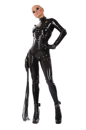 Skinhead woman in black latex catsuit with whip over white background
