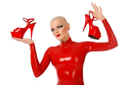 catsuit: Skinhead girl in red latex catsuit holding in hands sexy stilettos, on white background  Stock Photo