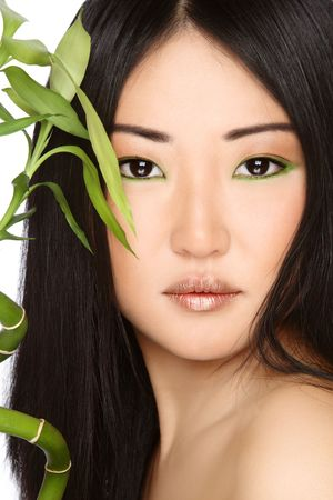 asian woman face: Close-up portrait of beautiful young asian girl with green bamboo