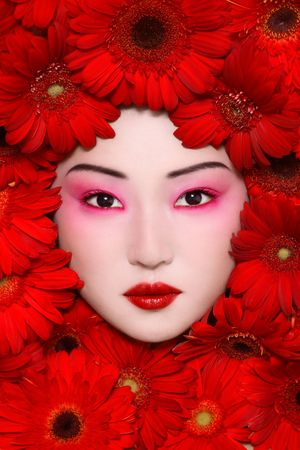 Beautiful young asian girl with stylish make-up and red flowers around face photo