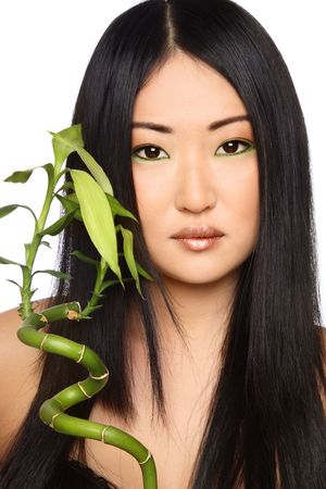 Portrait of beautiful young asian girl with green bamboo