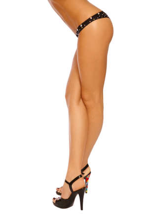 Slim legs of tanned sexy woman in black panties and stilettos on white background Stock Photo - 6935141