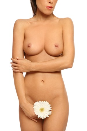 Torso of slim tanned sexy healthy naked woman with white flower in hand photo