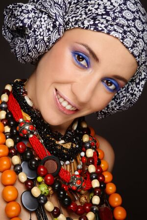 ethno: Portrait of young beautiful smiling woman in ethnic necklaces