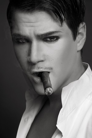 Black and white decadent portrait of young beautiful man smoking cigar photo