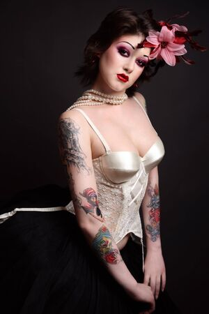 Beautiful slim young tattooed woman in ballet skirt and vintage corset