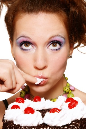 Close-up portrait of pretty young woman eating cake with funny expression Stock Photo - 7211832