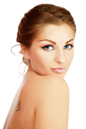 Portrait of beautiful woman healthy woman with trendy make-up and tattoo on her shoulder blade photo