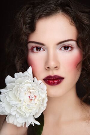 entice: Portrait of beautiful young woman with stylish make-up and white peony in hand