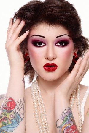 Close-up portrait of beautiful girl with stylish make-up and tattooed arms photo