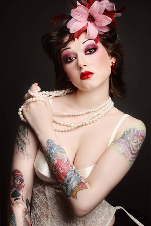 freaks: Beautiful slim young tattooed woman in ballet skirt and vintage corset