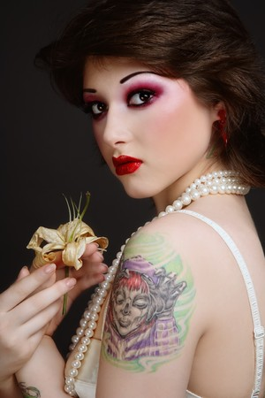 Portrait of beautiful young tattooed woman in vintage corset and pearls photo