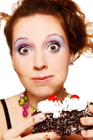 childishness: Close-up portrait of pretty young woman eating cake with funny expression