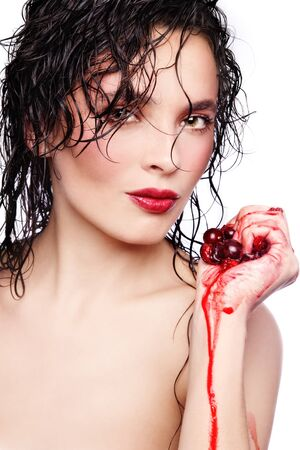 Portrait of young beautiful hot woman squeezing cherries in hand photo