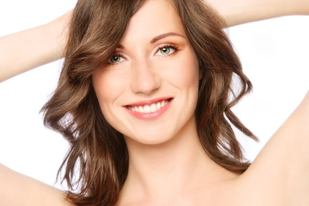 free radicals: Beautiful happy smiling young healthy woman touching her hair, on white background