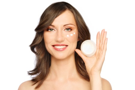 free radicals: Beautiful happy smiling young healthy woman with cream on her face and cosmetic jar in hand, on white background Stock Photo