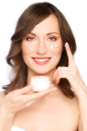 free radicals: Beautiful happy smiling young healthy woman with cosmetic jar in hand applying cream, on white background