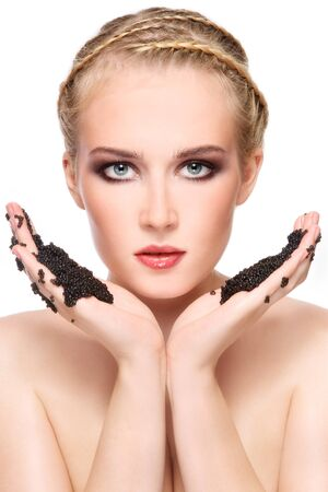 Portrait of young beautiful blond woman with stylish make-up holding black caviar in hands photo