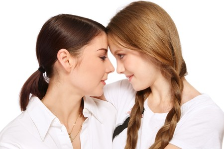 misunderstanding: Attractive mother and pretty teen daughter talking, on white background