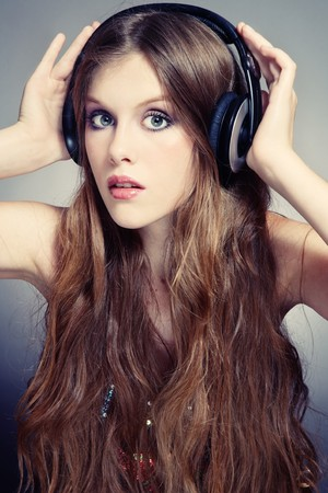 Beautiful stylish teen girl in headphones listening music  photo