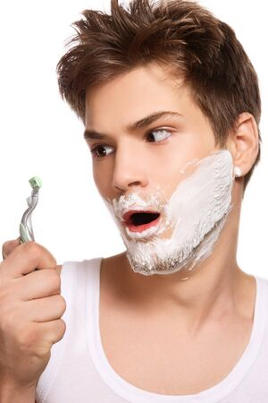 Portrait of young beautiful sexy man shaving with shocked expression photo