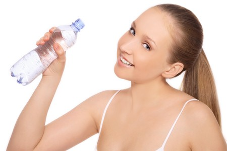 free radicals: Young blond attractive healthy smiling woman with bottle of water in hand, on white background