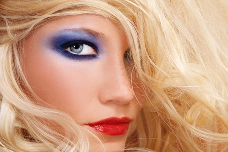 allure: Close-up shot of young beautiful woman with long blond hair and stylish make-up