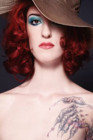 Glamorous portrait of young redhead woman in hat with tattoo on her shoulder photo