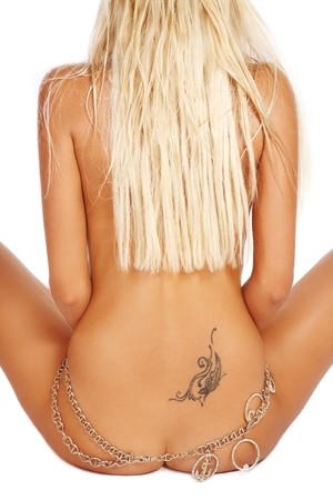 Straight back of tanned slim sexy naked blond woman with tattoo and chain on hips Stock Photo - 7956527
