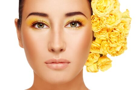 Close-up portrait of young beautiful woman with stylish make-up and bright yellow roses in hair