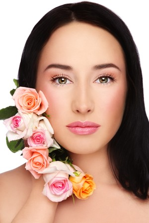 Portrait of young beautiful woman with clear make-up and fresh tender roses over white background