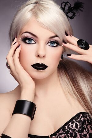 glam: Beautiful young sexy blond girl with stylish black make-up and fancy accessories
