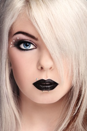freaky: Close-up portrait of beautiful young blond girl with fancy black make-up and piercing