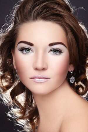 glamorous: Beautiful young girl with glowing white make-up and curly hairstyle