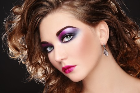 eighties: Beautiful young girl with glowing colorful disco make-up and curly hairstyle