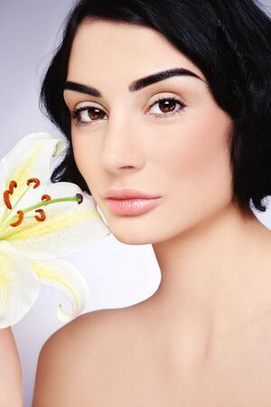Close-up portrait of beautiful brunette with natural clear make-up and lily photo