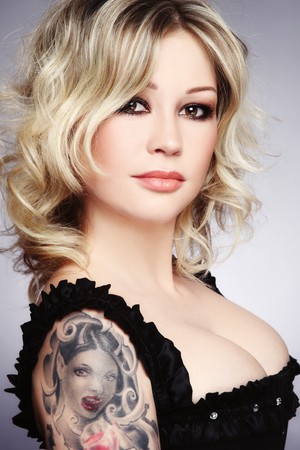 Beautiful sexy blonde woman in corset with tattoo on shoulder Stock Photo - 8085730