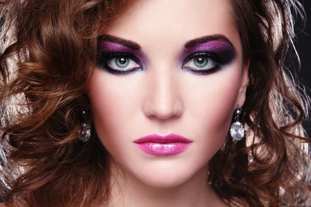 glamourous: Beautiful young girl with glowing colorful disco make-up and curly hairstyle