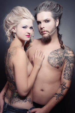 freaks: Pierced tattooed man and woman with old-fashioned make-up and hairstyle  Stock Photo