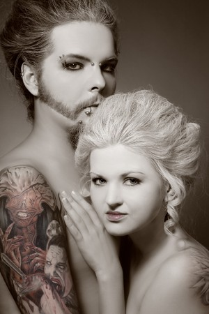 freaks: Duotone portrait of pierced tattooed man and woman with old-fashioned make-up and hairstyle